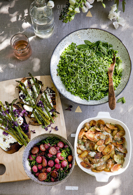 Outdoor Easter brunch table with pea salad and roasted potatoes