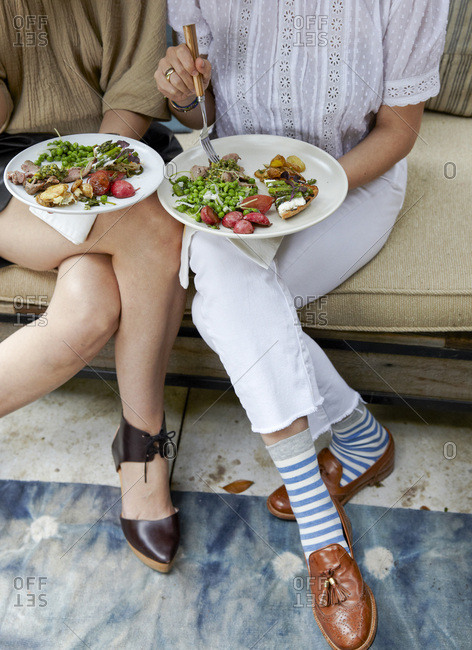 Women eating outdoors at party with plates on their laps