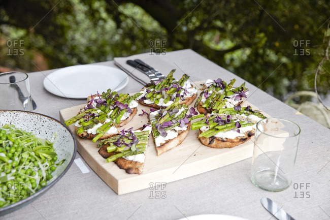 Toast with ricotta and asparagus on wood board on table