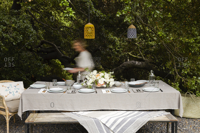 Woman setting table for outdoor Easter brunch