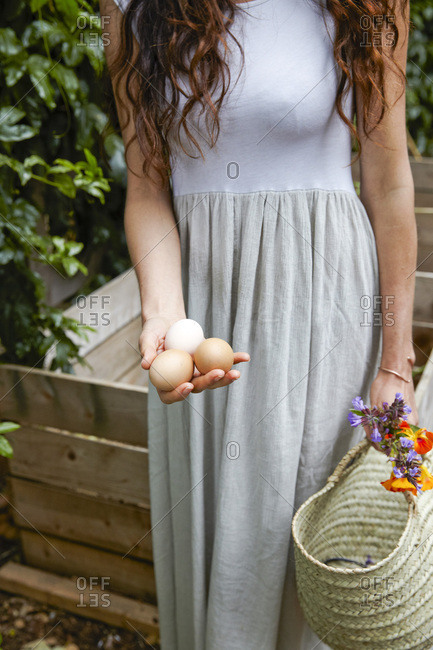 Woman gathering eggs and flowers from garden