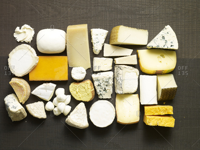 Variety of different cheeses on black wooden surface