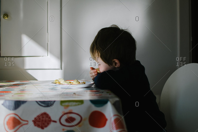 Young boy eating snack at table