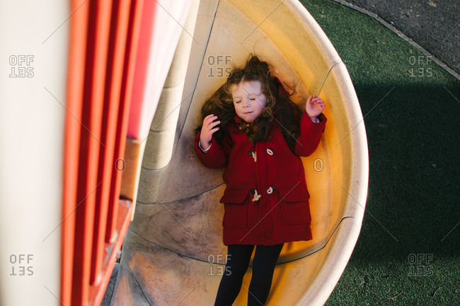 High angle view of girl sliding down curved slide