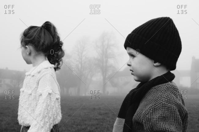 Two kids standing in fog in black and white