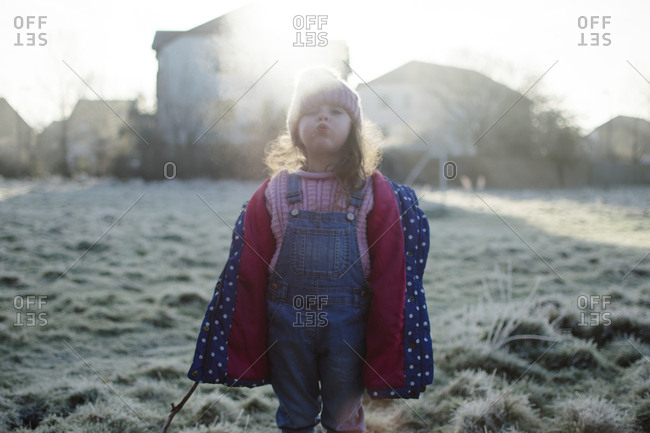Little girl blowing air into chilly winter air
