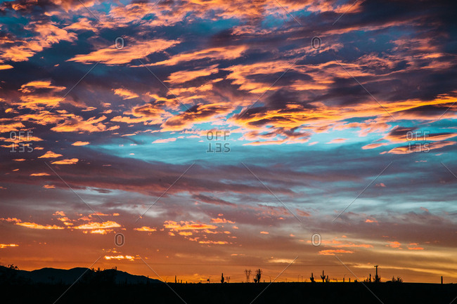 Colorful sunset shining on clouds over desert landscape