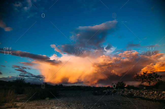 Sunset and cloudy sky over desert landscape