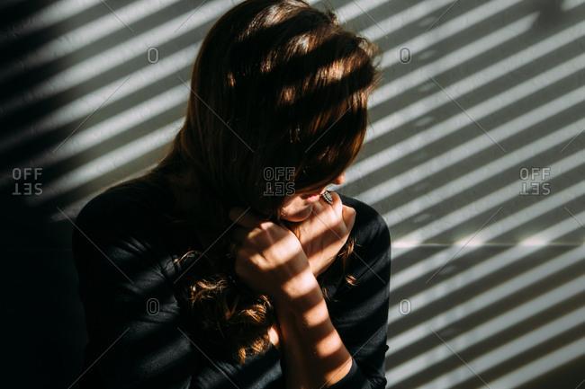 Portrait of a woman pulling hair in window light