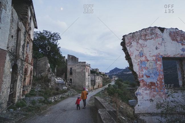 Mother and daughter walking through Gairo Vecchio, Italy
