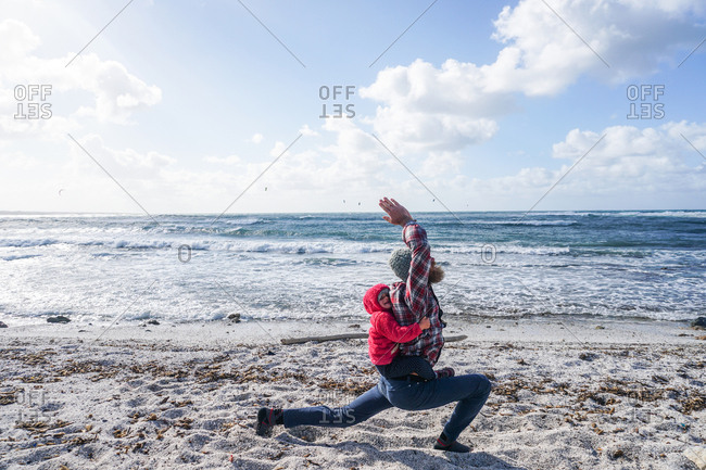 Man doing yoga pose by the ocean with daughter on his back