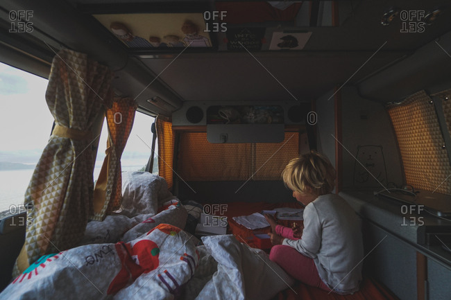 Girl riding in back of a campervan on a road trip