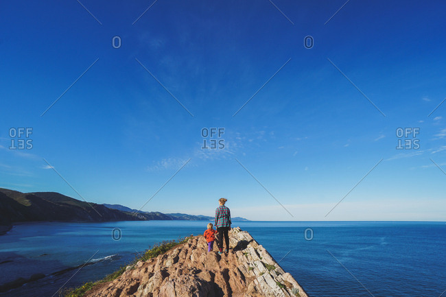Mother and daughter looking out to ocean from Zumaia, Spain