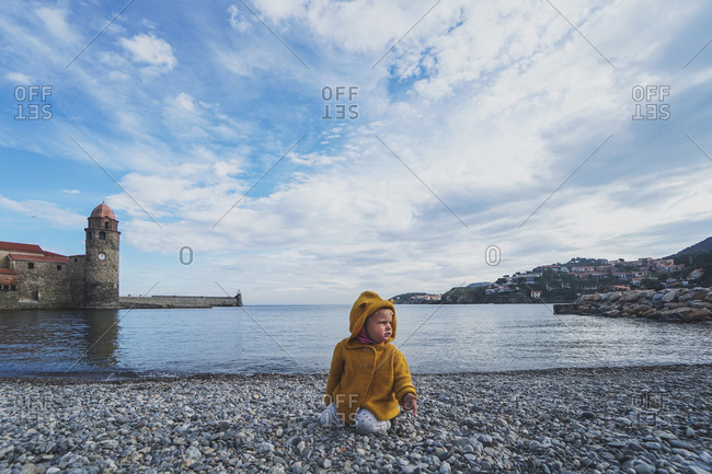 Child playing on the shores by the Church of Our Lady of the Angels and fort, in Collioure, France