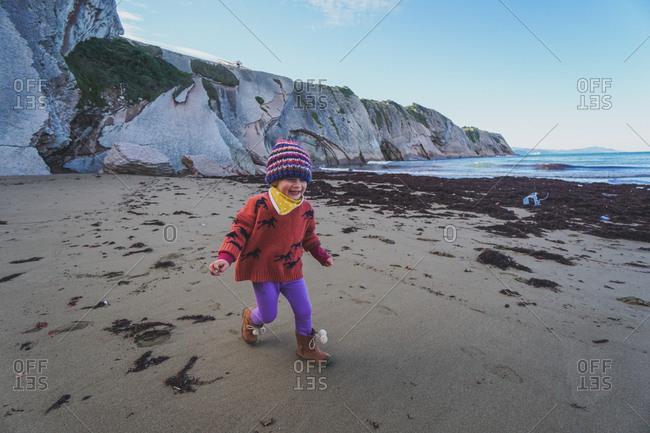 Girl running  on a beach in Zumaia, Spain