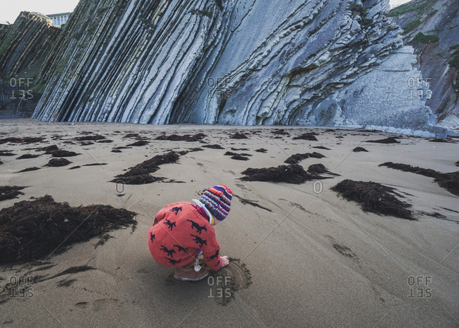 Girl playing in sand by flysch on beach in Zumaia, Spain
