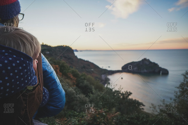 Woman carrying baby in carrier overlooking Gaztelugatxe Island in Biscay Spain