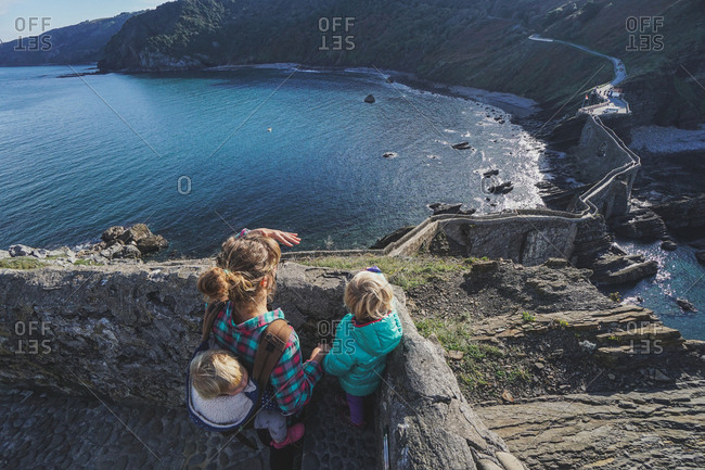 Woman and daughters overlooking stone bridge from Gaztelugatxe Island in Biscay Spain