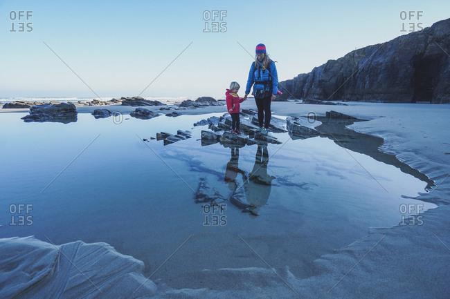 Mother and daughter looking at water at Playa de las Catedrales Ribadeo, Spain