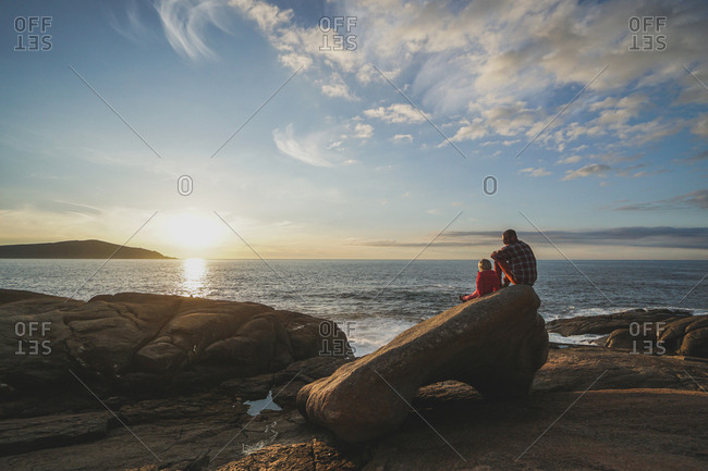 Man watching sunrise by the ocean with daughter