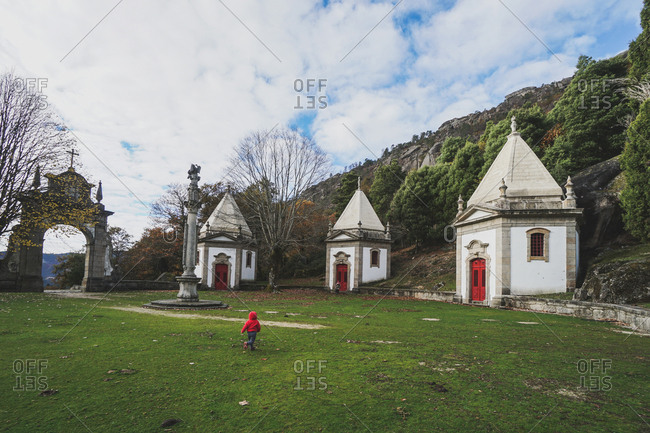 Toddler walking in cemetery with red and white crypts