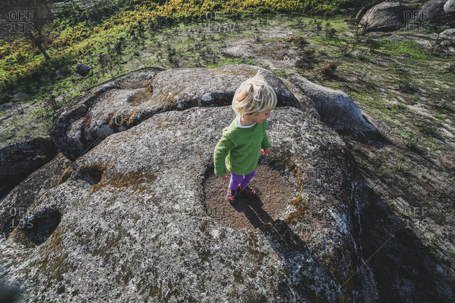 Girl walking on large rock formation