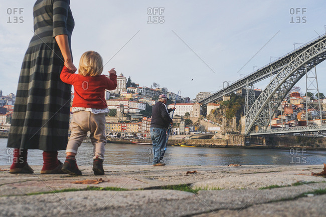 Mather and child watching fisherman by the Dom Luis I Bridge, Porto, Portugal