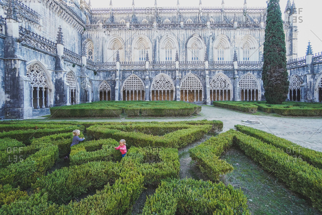 Children playing in bushes at the Batalha Monastery, Batalha, Portugal