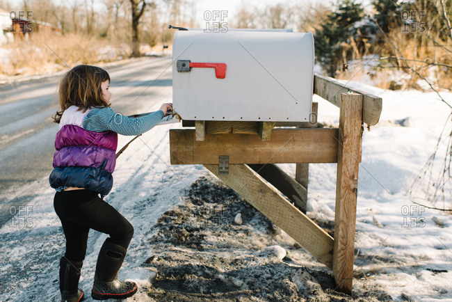Girl looking in mailbox on side of a snowy road