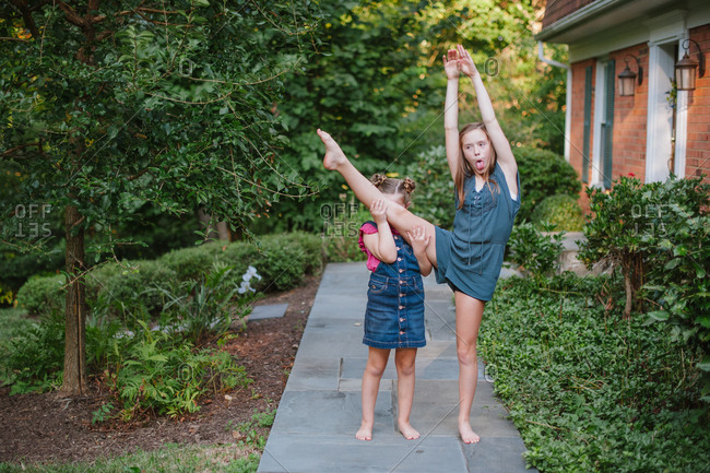 Girls lifting sister's leg in front yard