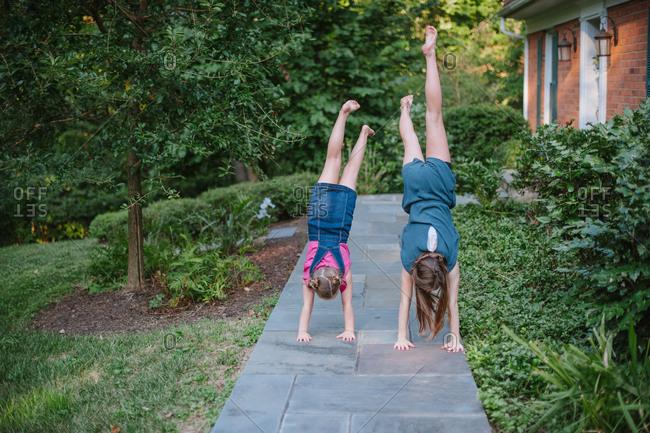 Girls doing handstands on sidewalk