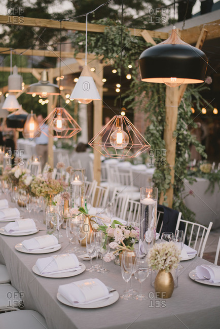 Light fixtures glowing over wedding tables