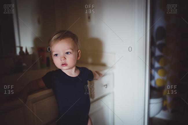 Toddler boy staring off in bathroom
