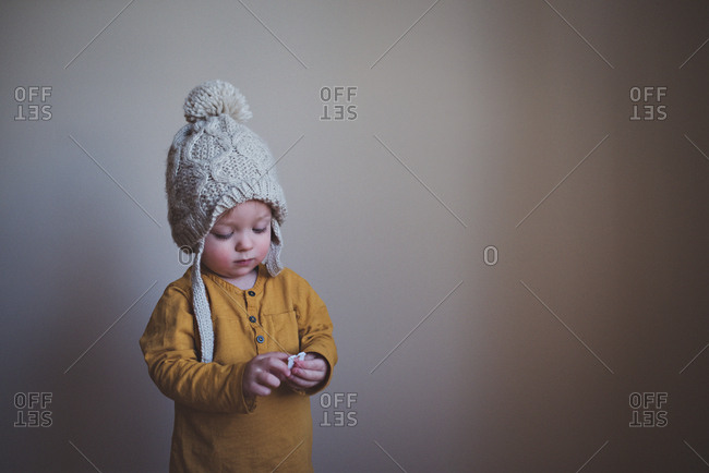 Toddler holding paper wearing knit hat