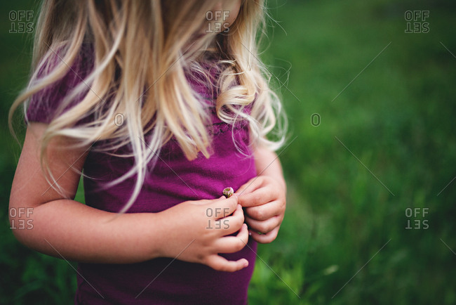 Girl holding small flower outside