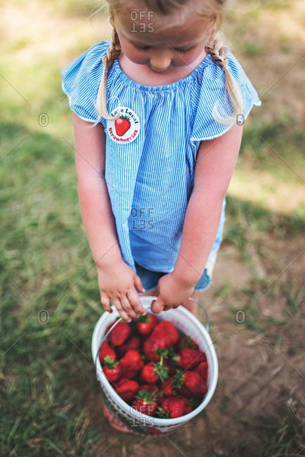 Girl with bucket of strawberries