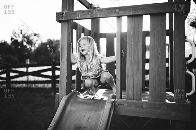 Girl on yard slide in sunlight