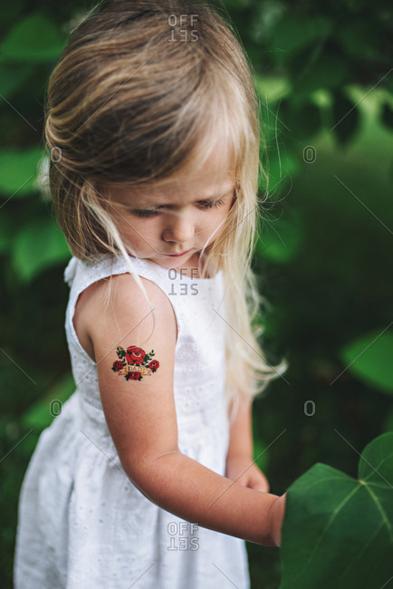 Girl with temporary tattoo on arm