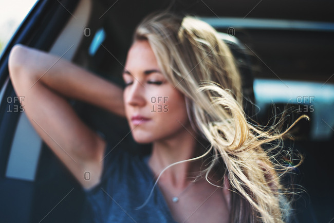 Woman with hair blowing in car