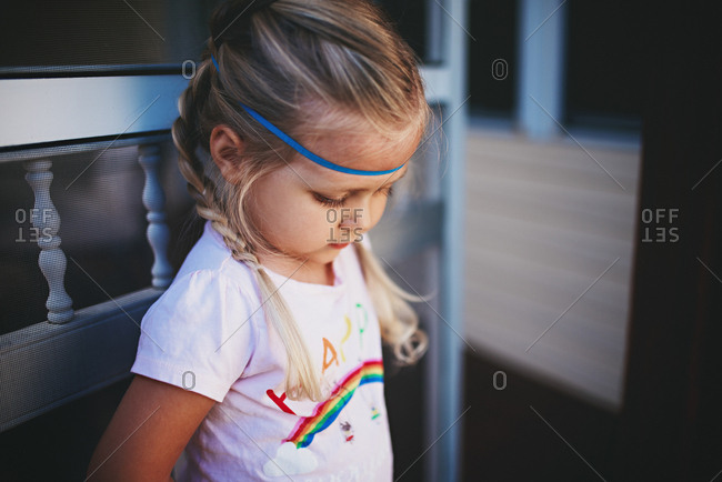 Girl with headband at a screen door