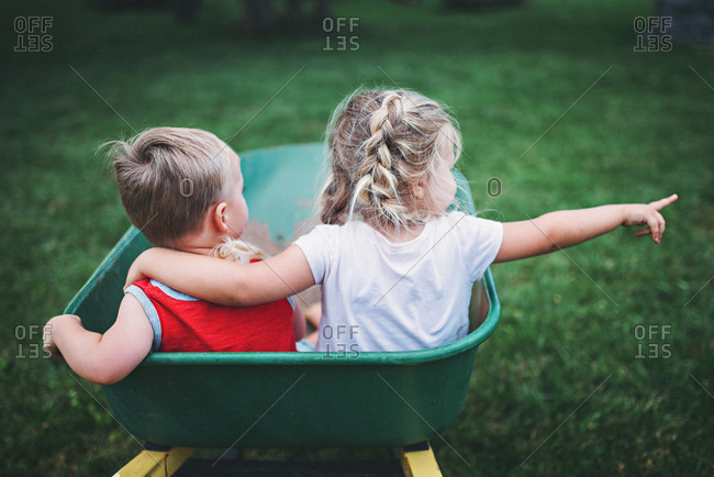 Two kids in a wheelbarrow together