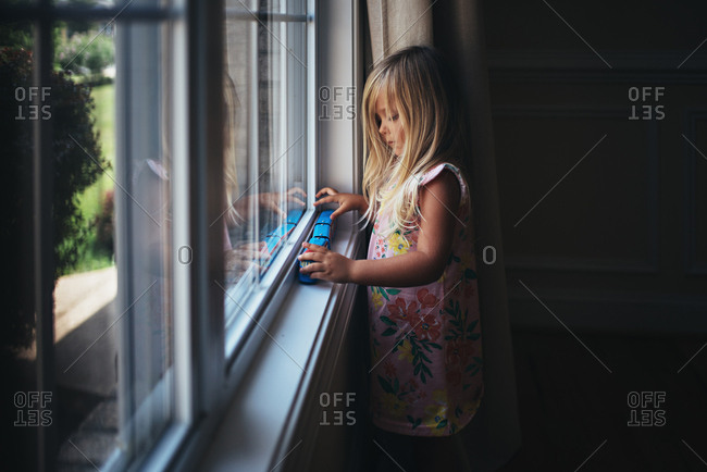 Girl playing with toys on window sill