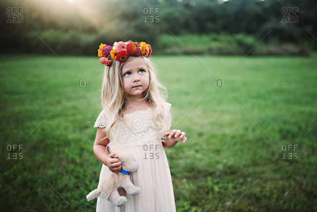 Girl in floral crown standing in field
