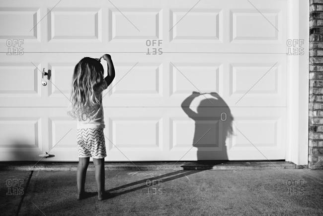 Girl making shadow puppet on garage