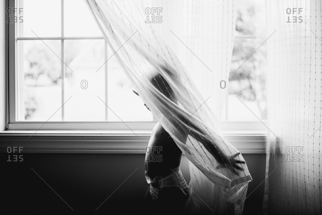 Boy in sheer curtains by window