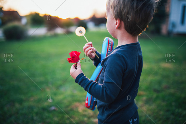 Boy with dandelion in sunrise