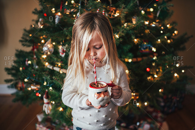 Girl drinking hot cocoa by Christmas tree