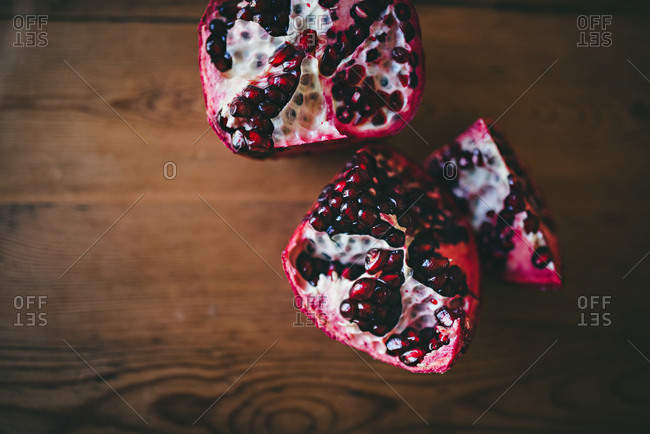 Pomegranate pieces on wood background