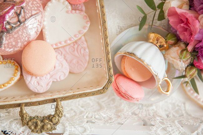 Heart shaped cookies and macaroons on a platter and teacup