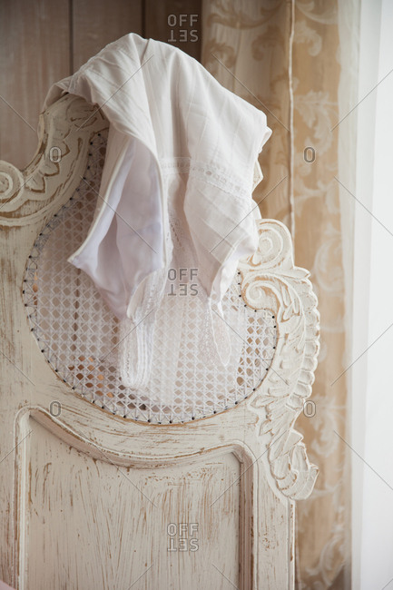 White cotton dress hanging over the back of a white distressed screen